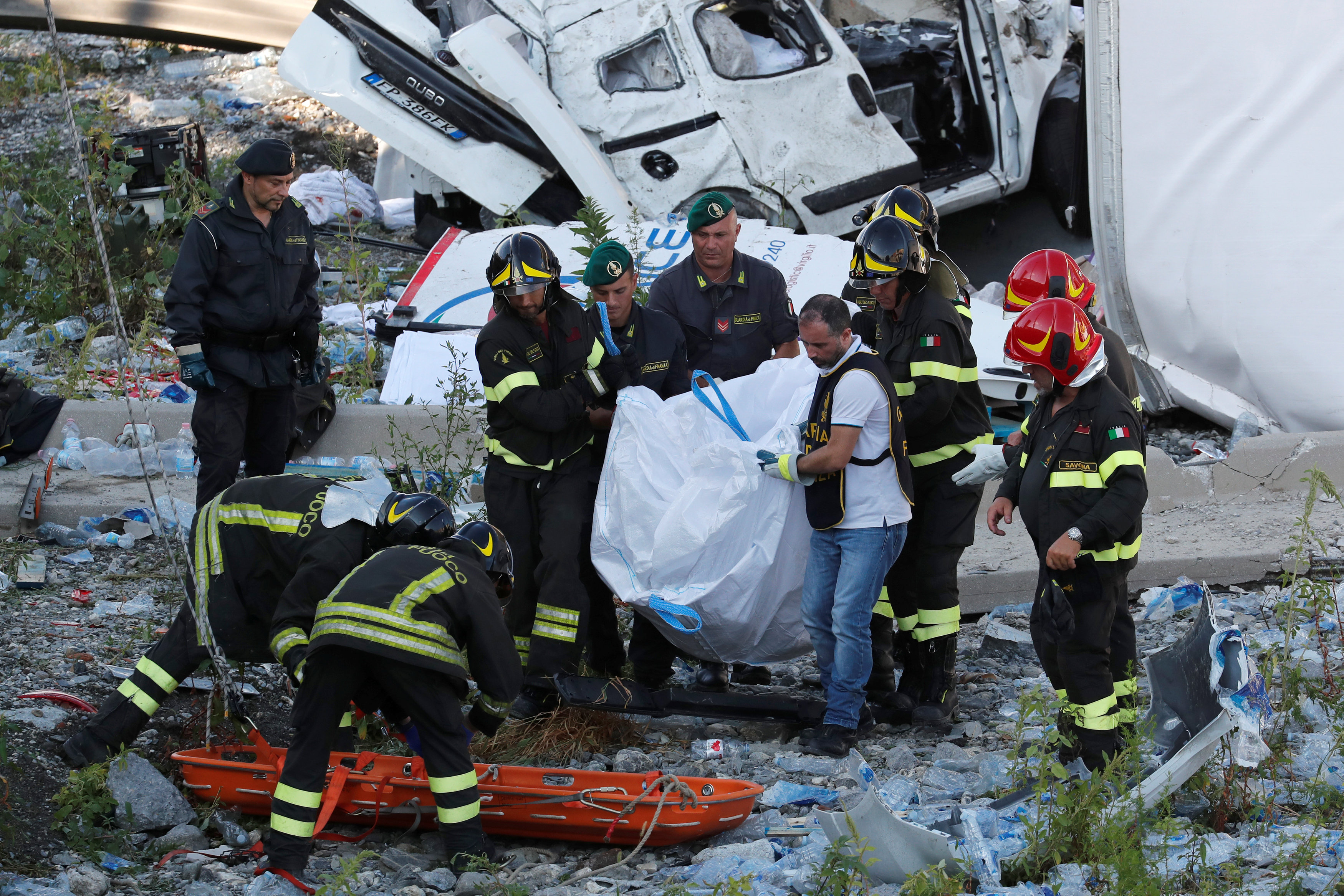 Firefighters carry body at collapsed Morandi Bridge site in Genoa