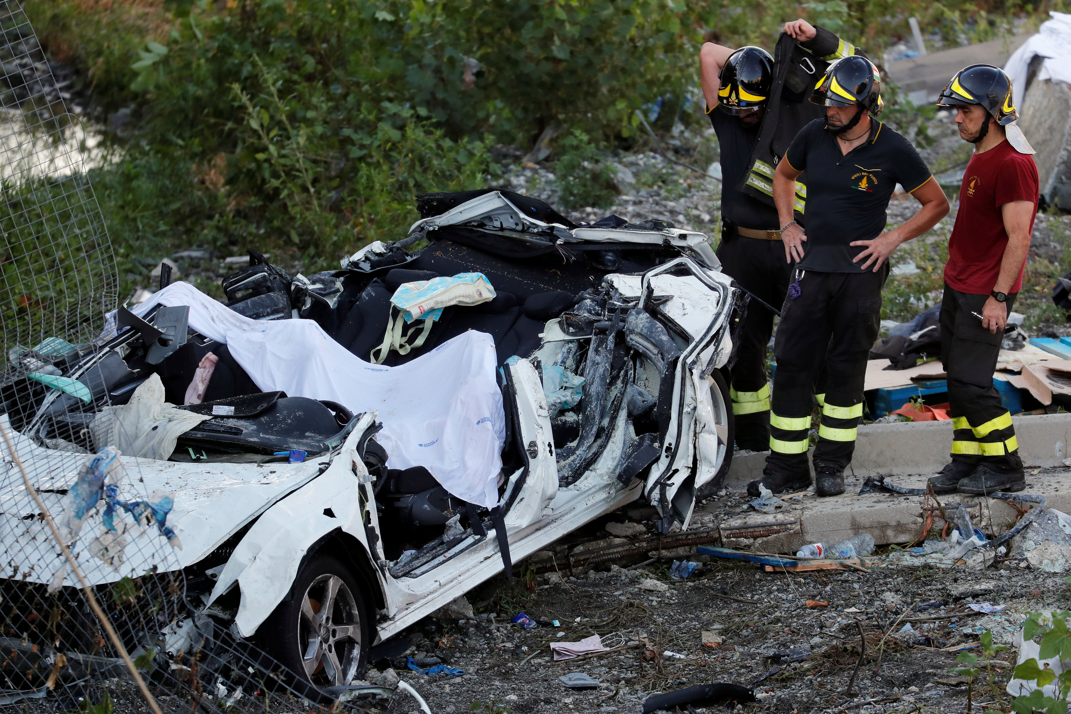 Firefighters stand next to crushed car at collapsed Morandi Bridge site in Genoa