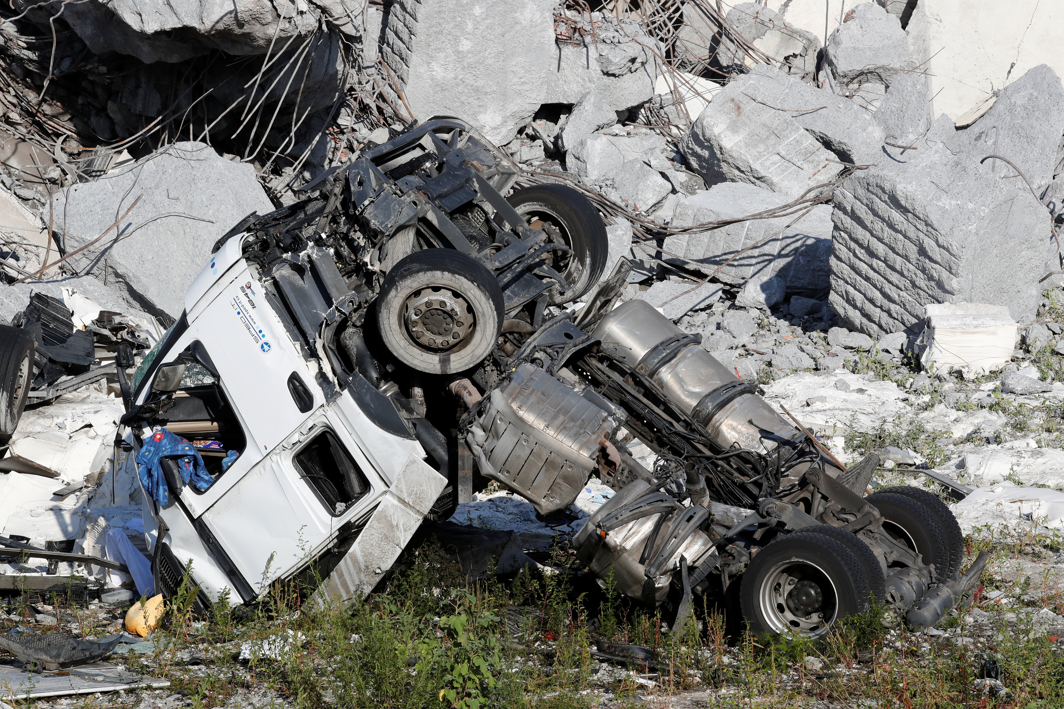 Crushed truck is seen at the collapsed Morandi Bridge site in the port city of Genoa