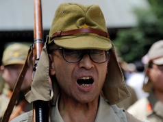 A man dressed as Japanese imperial army soldier shouts an order as he marches in front of Yasukuni Shrine in Tokyo