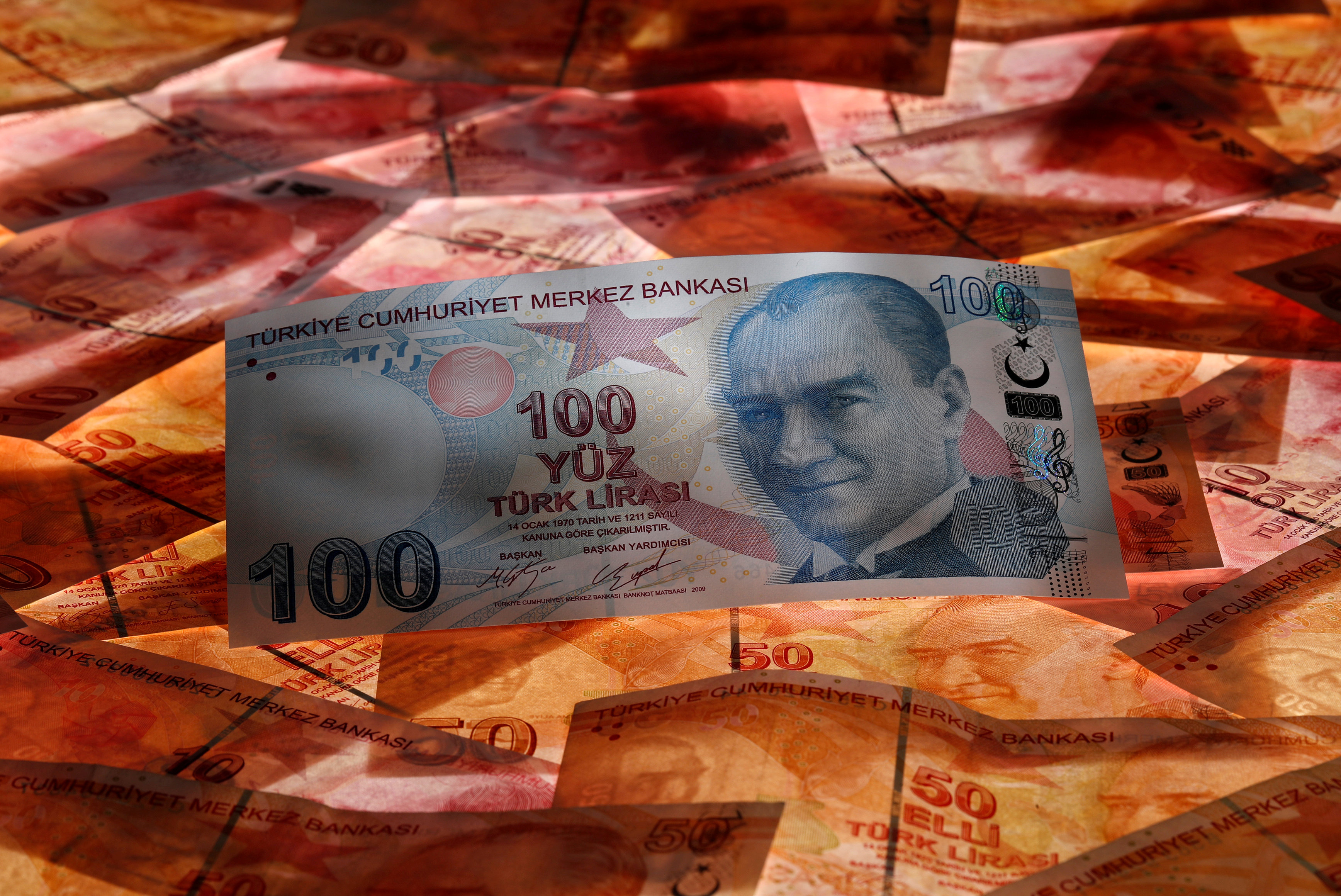 A 100 Turkish lira banknote is seen on top of 50 Turkish lira banknotes in this picture illustration in Istanbul