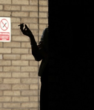 A woman smokes in the shadows outside Southwark Crown Court in central London