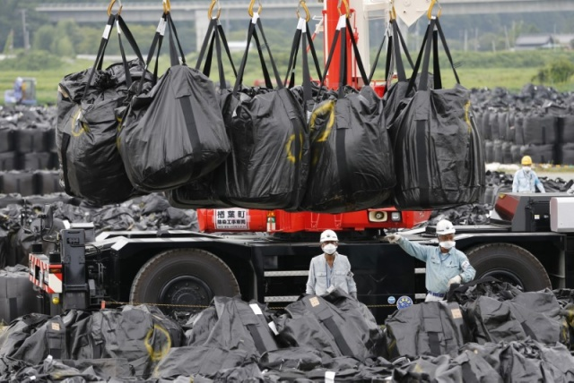 Workers move waste containing radiated soil, leaves and debris from the decontamination operation at a storage site in Naraha town
