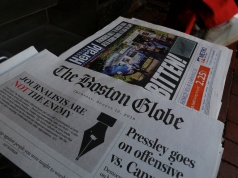 The front page of the Boston Globe newspaper references their editorial defense of press freedom at a newsstand in Cambridge