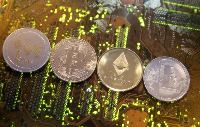 Representations of the Ripple, Bitcoin, Etherum and Litecoin virtual currencies are seen on motherboard in this illustration picture