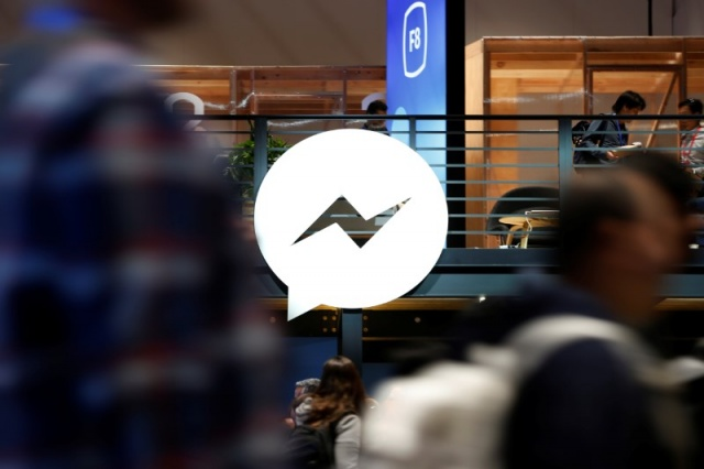 Attendees walk past a Facebook Messenger logo during Facebook Inc's annual F8 developers conference in San Jose, California