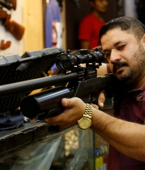 A man checks a weapon before he buys at a weapons shop in Baghdad