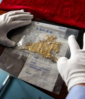 Police officer displays a retrieved cultural relic which was stolen from an ancient burial site, at a police station in Dulan
