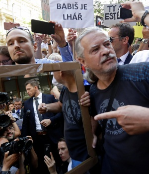 Demonstrators hold a mirror as they protest against Czech PM Babis during a ceremony to commemorate the 50th anniversary of the Soviet-led invasion into foprmer Czechoslovakia in Prague