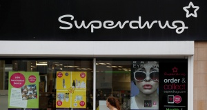 A woman walks past a branch of Superdrug in Loughborough