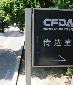 A man talks on the phone near a sign for the reception office of China's Food and Drug Administration