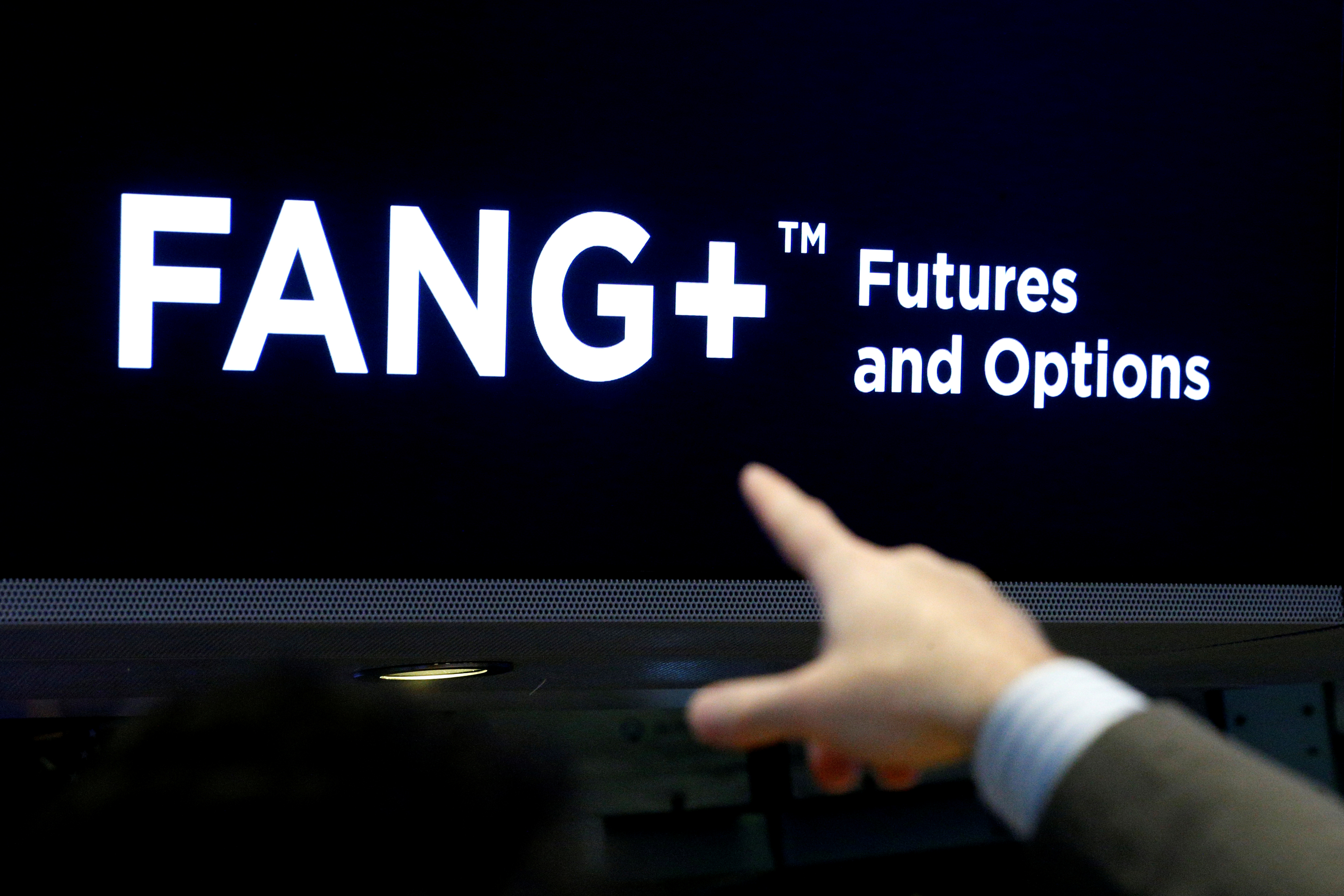 A trader points to a screen that displays FANG+, group of highly-traded technology and tech-enabled companies, on the floor of the NYSE in New York