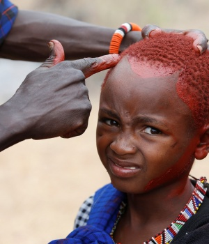 A Maasai boy is painted with red ochre pigment during an initiation into an age group ceremony near the town of Bisil, Kajiado county