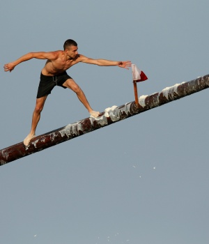 "A competitor tries to grab a flag on the ""gostra"", a pole covered in lard, during the celebrations of the religious feast of St Julian, patron of the town of St Julian's"