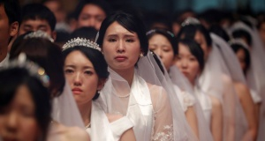 A bride reacts during a mass wedding ceremony of the Unification Church at Cheongshim Peace World Centre in Gapyeong