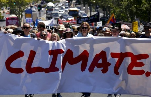 People hold placards and banners as they participate in a march ahead of the Paris World Climate Change Conference, along the main street of Adelaide, South Australia