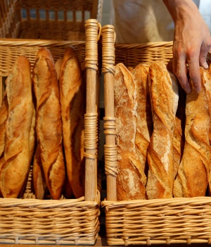 A French baker places freshly-baked baguettes in wicker baskets in his shop in Strasbourg