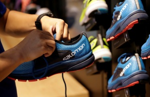 A shop assistant holds a shoe at a Salomon store in Beijing