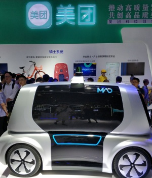 Visitors look at a Meituan Autonomous Delivery (MAD) vehicle of Chinese food delivery platform Meituan-Dianping, at the first Smart China Expo in Chongqing