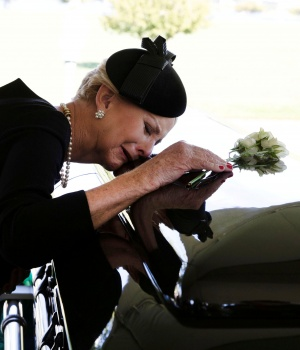Cindy McCain lays her head on the casket of Sen. McCain during a burial service at the cemetery at the United States Naval Academy in Annapolis