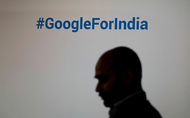 A man walks past a Google hashtag during an event in New Delhi