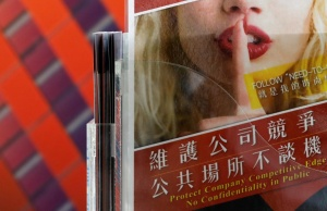 A leaflet that asks employees to protect company confidentiality is seen at a reception in a chip company, in Hsinchu