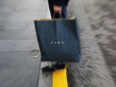 A mans hold a Zara shopping bag outside a Zara store, an Inditex brand, in central Madrid