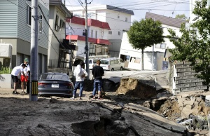 People look at an area damaged by an earthquake in Sapporo
