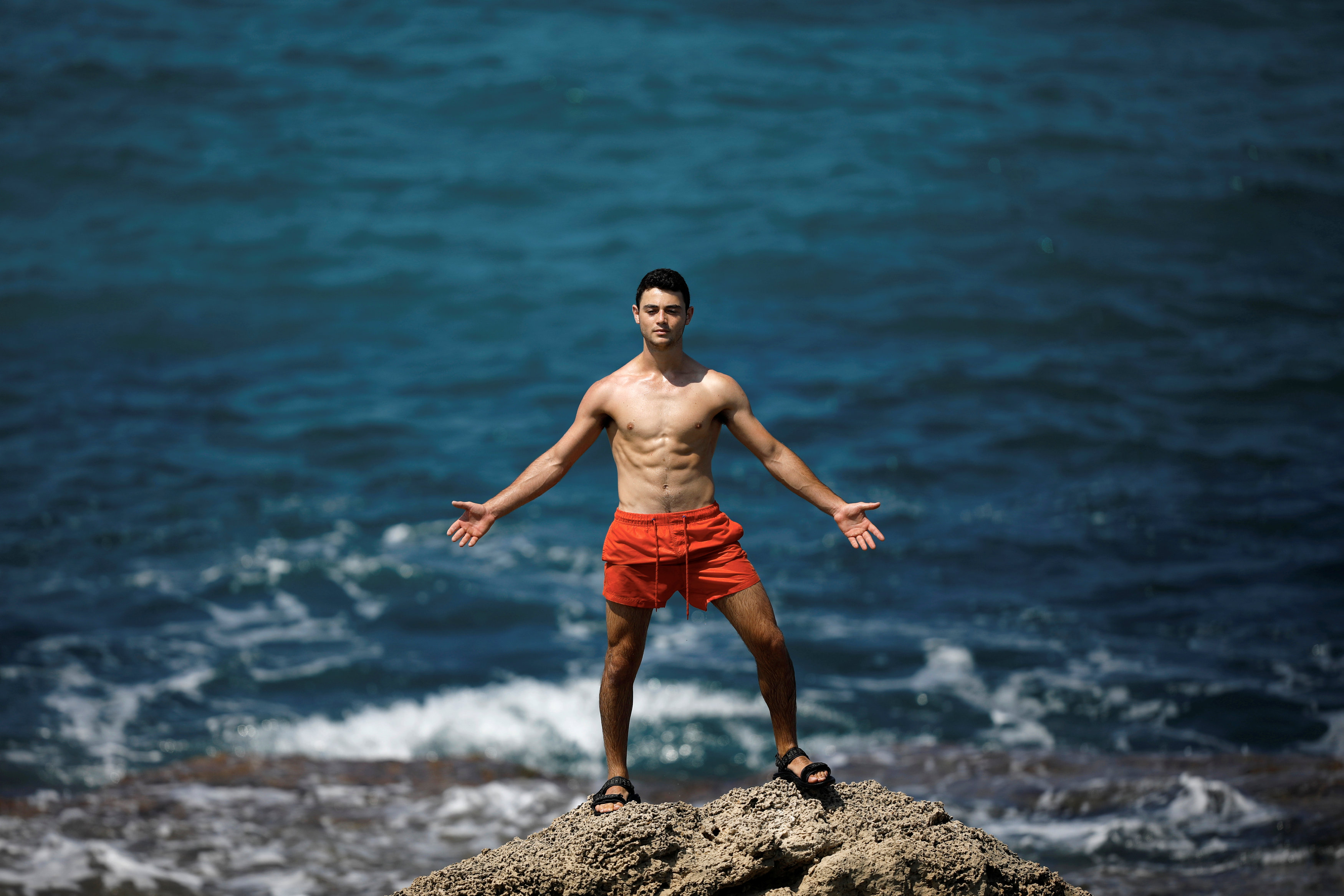 Sunbather poses for a friend as he stands atop a rock in the Mediterranean Sea at Dor Beach