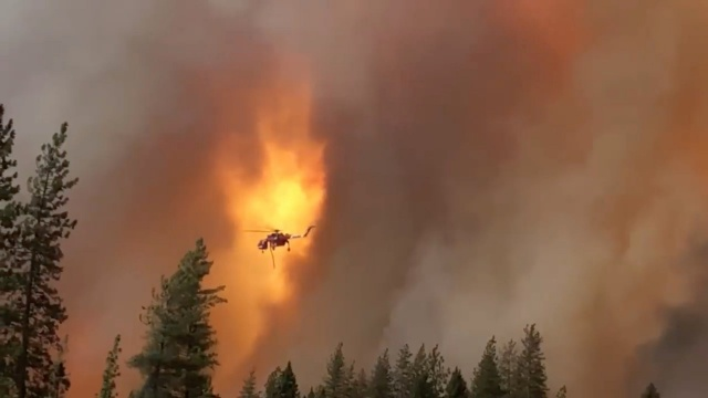 A helicopter drops water on a forest fire in Shasta County in California