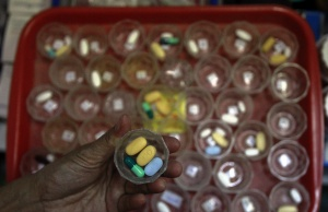 Nurse prepares doses of drugs for HIV and AIDS patients at Buddhist temple Wat Prabat Namphu in Lopburi province