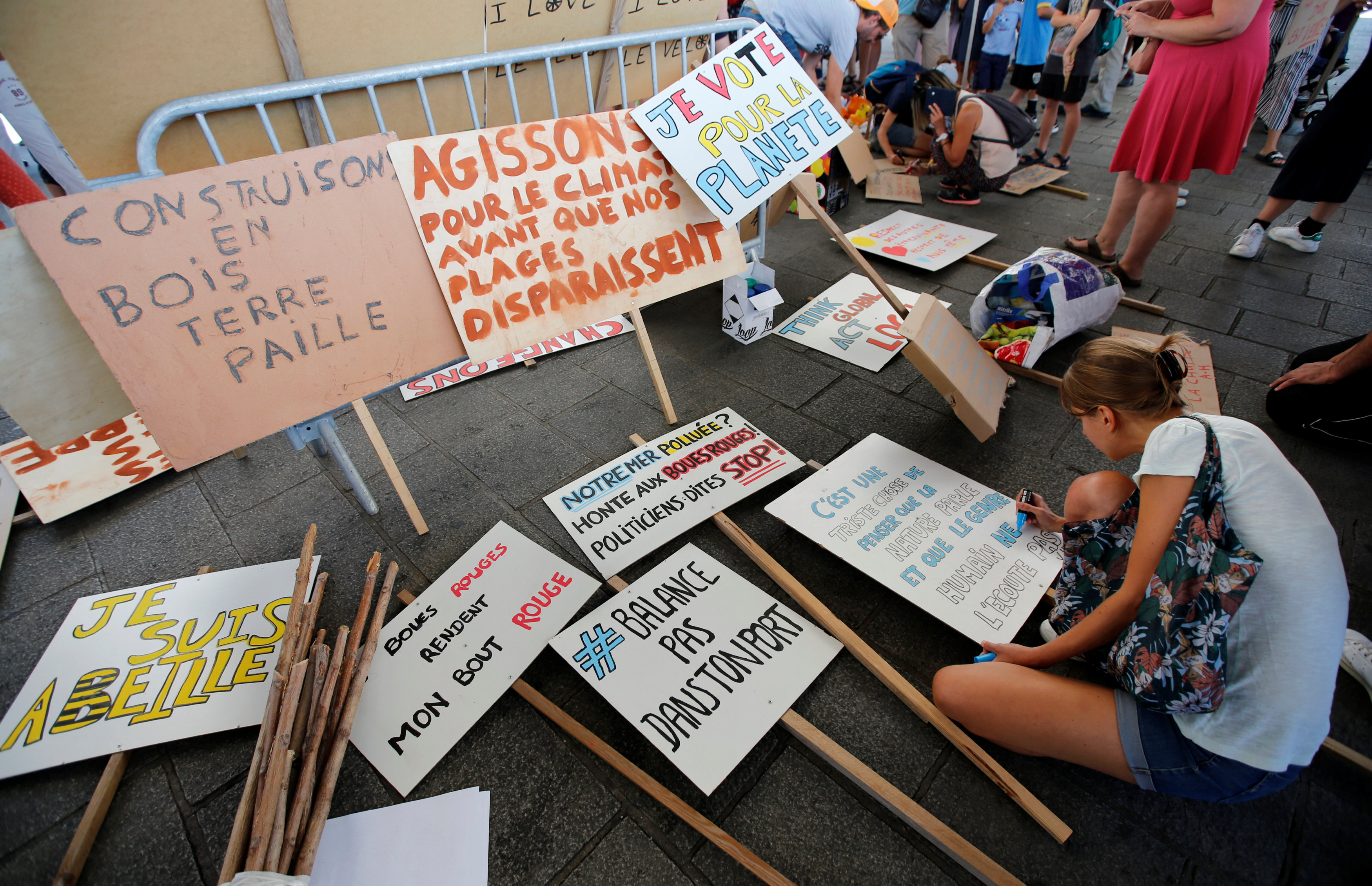Environmental activists prepare placards as they gather to urge world leaders to take action against climate change in Marseille