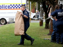 A police officer carries a bag from a property where five people were found dead in a suburb of Perth