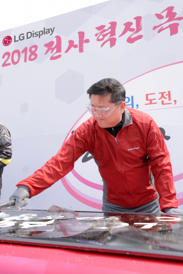 LG Display Vice Chairman Han Sang-beom smashes discarded 55-inch LCD panel with a hammer during an event at their factory in Paju