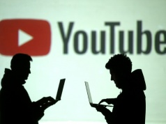 Silhouettes of mobile device users are seen next to a screen projection of Youtube logo in this picture illustration