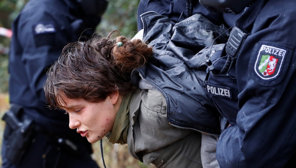 Policemen detain an activist as they attempt to clear the area at the