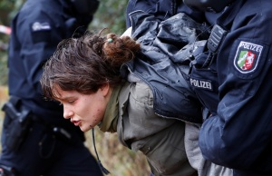 "Policemen detain an activist as they attempt to clear the area at the ""Hambacher Forst"" in Kerpen-Buir near Cologne"