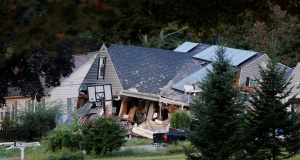 A home sits collapsed where a man died in a series of gas explosions in Lawrence