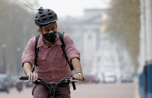 A cyclist wears a mask as he cycles near Buckingham Palace in London