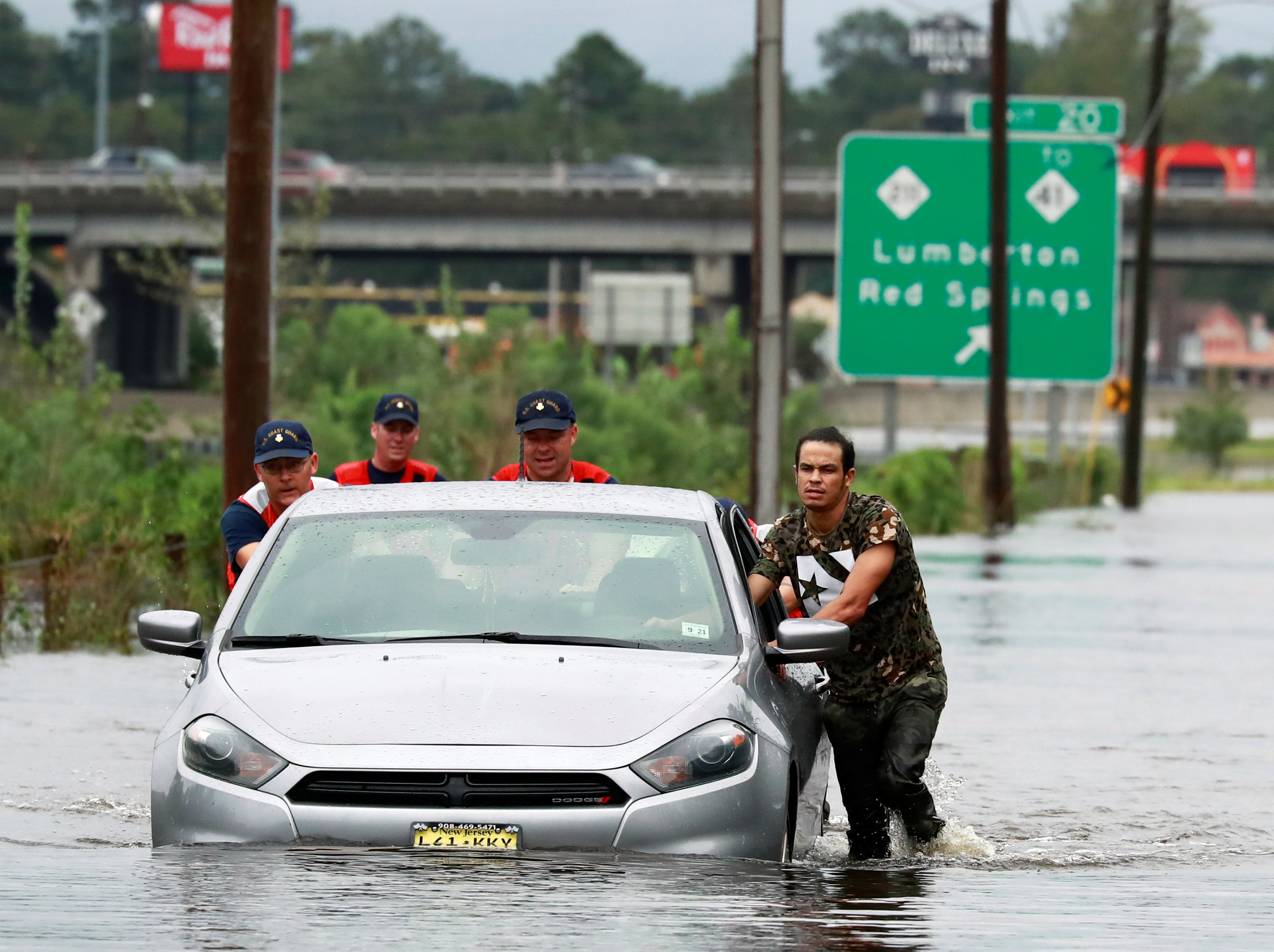 Members of the Coast Guard help a stranded motorist in the flood waters caused by Hurricane Florence in Lumberton