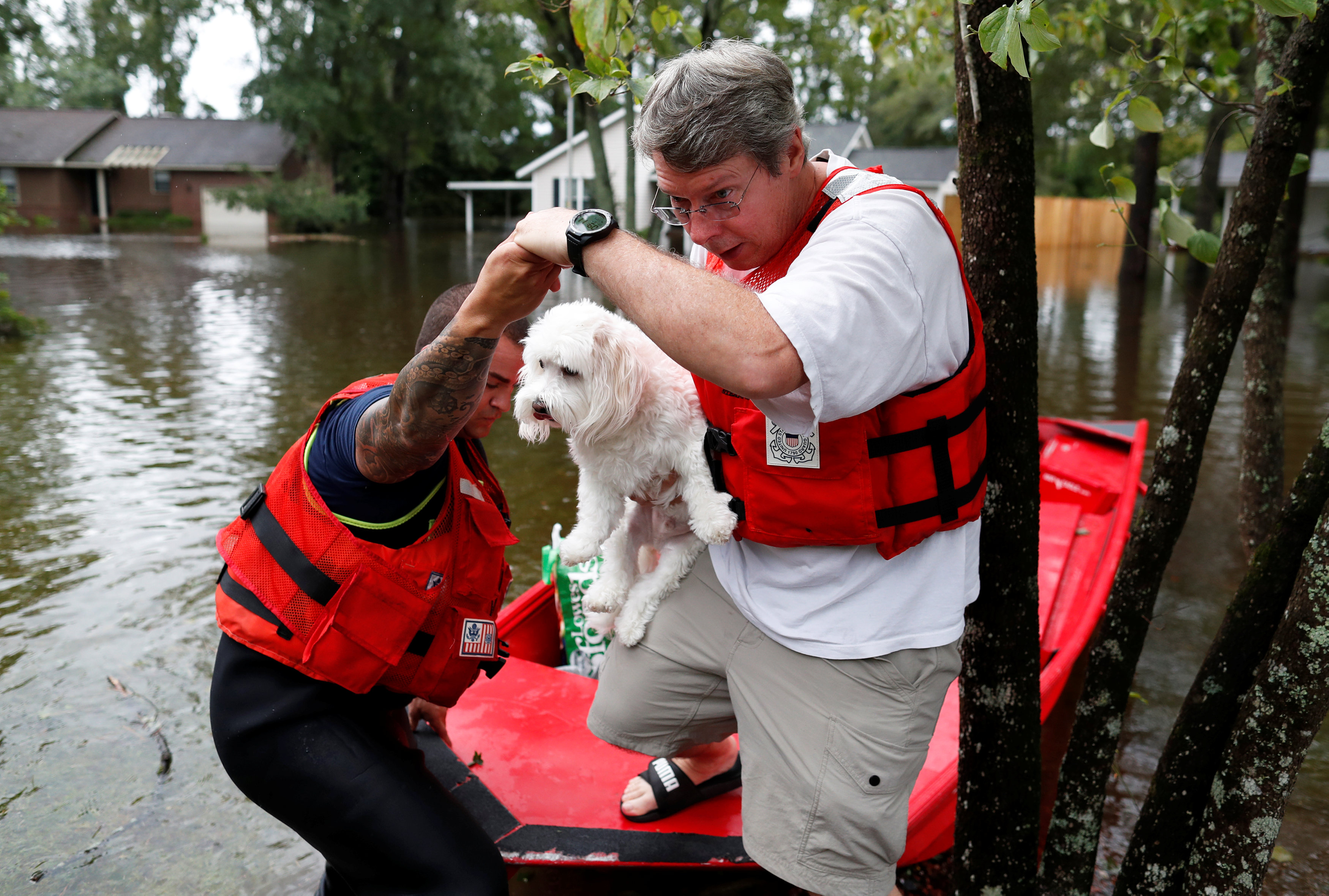 Roger Hedgpeth, carrying his dog Bodie, gets help getting to higher ground via the United States Coast Guard during Tropical Storm Florence in Lumberton