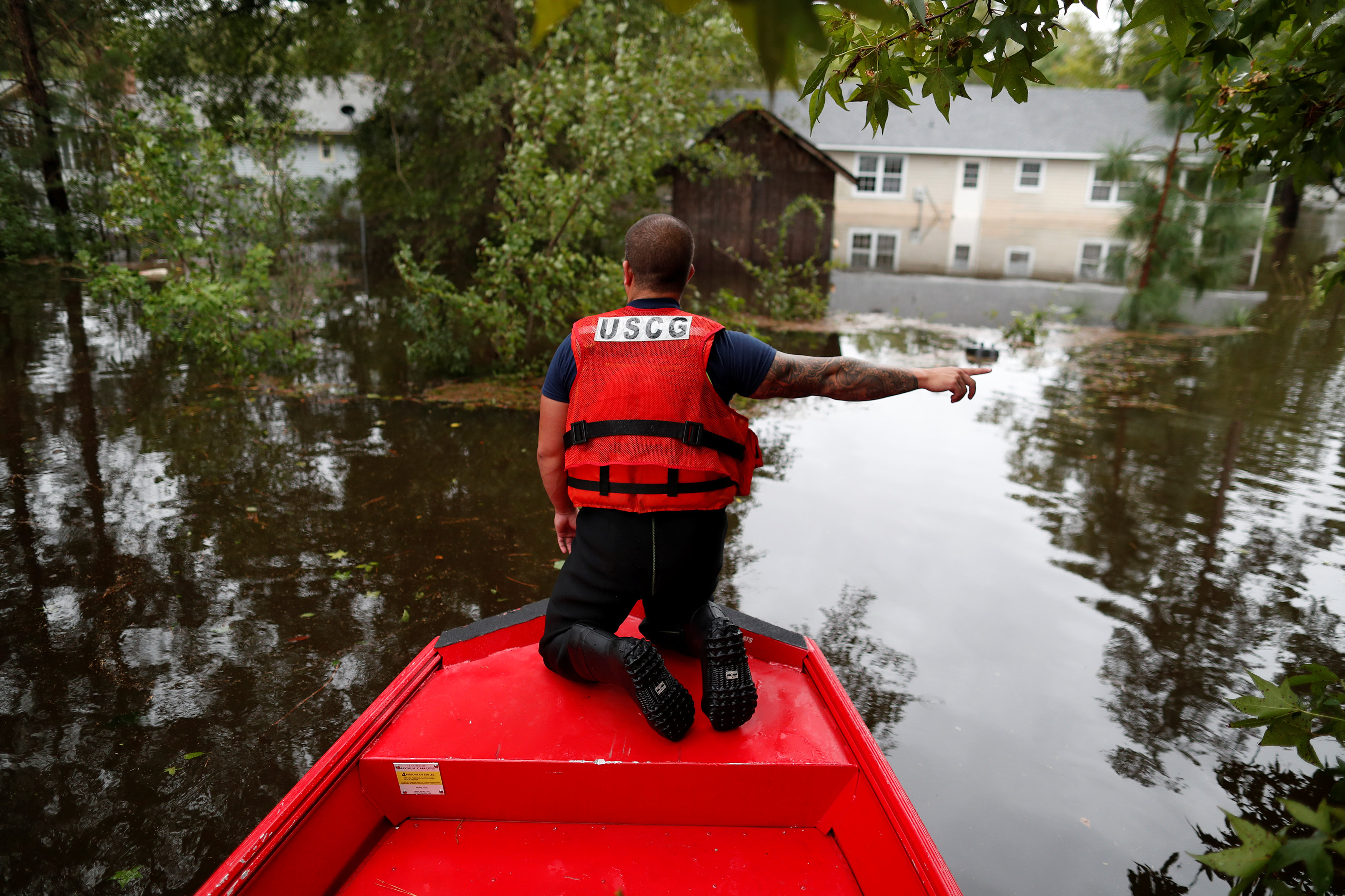 U.S. Coast Guard Petty Officer David Kelley directs a boat during Tropical Storm Florence in Lumberton