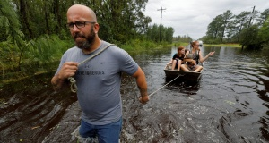 A volunteer from the community pulls a boat holding a mother and several of her children during their rescue from rising flood waters in the aftermath of Hurricane Florence, in Leland, North Carolina