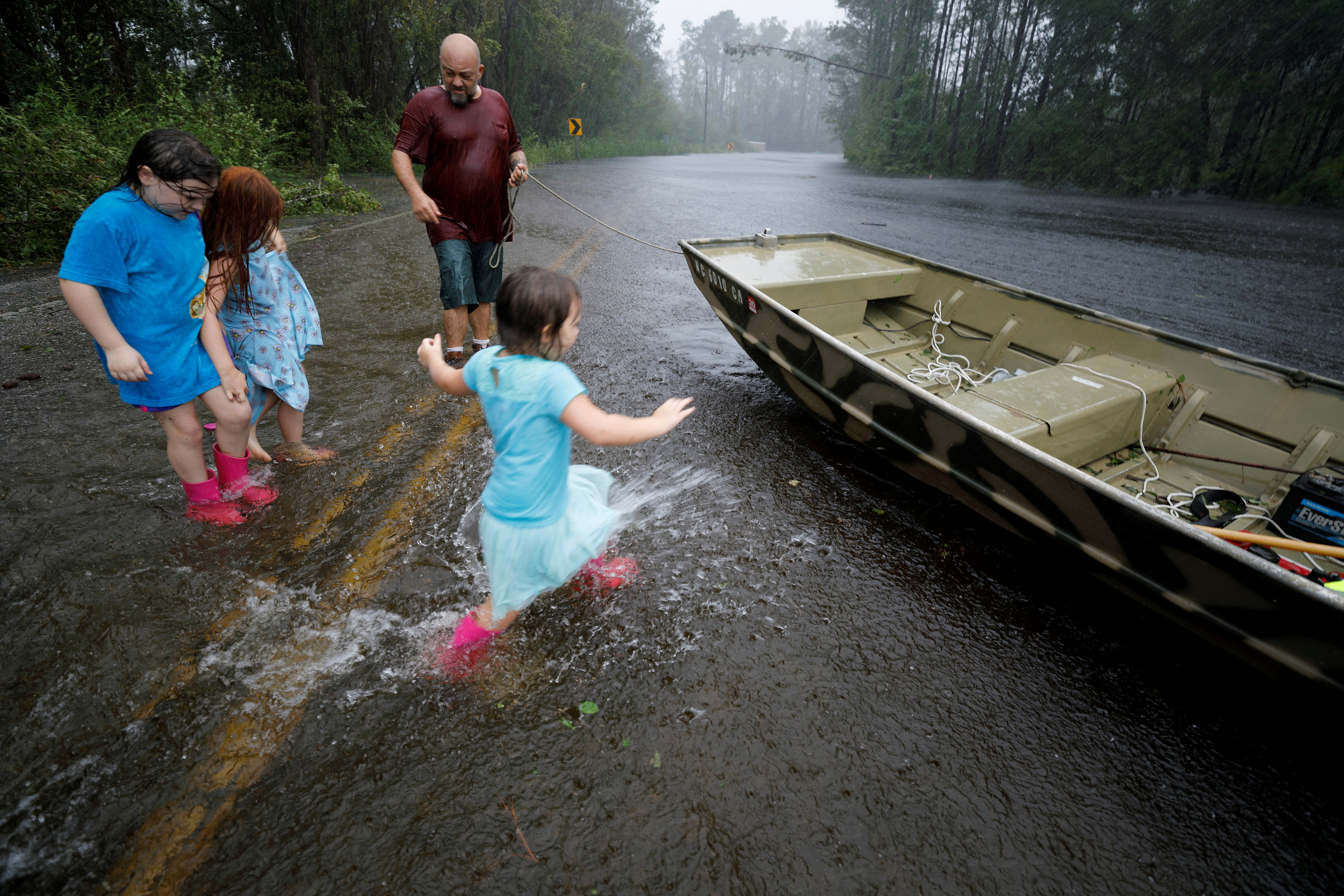 Iva Williamson runs through flood waters submerging a street to a boat as others wait to board during their rescue from rising flood waters in the aftermath of Hurricane Florence in Leland, North Carolina
