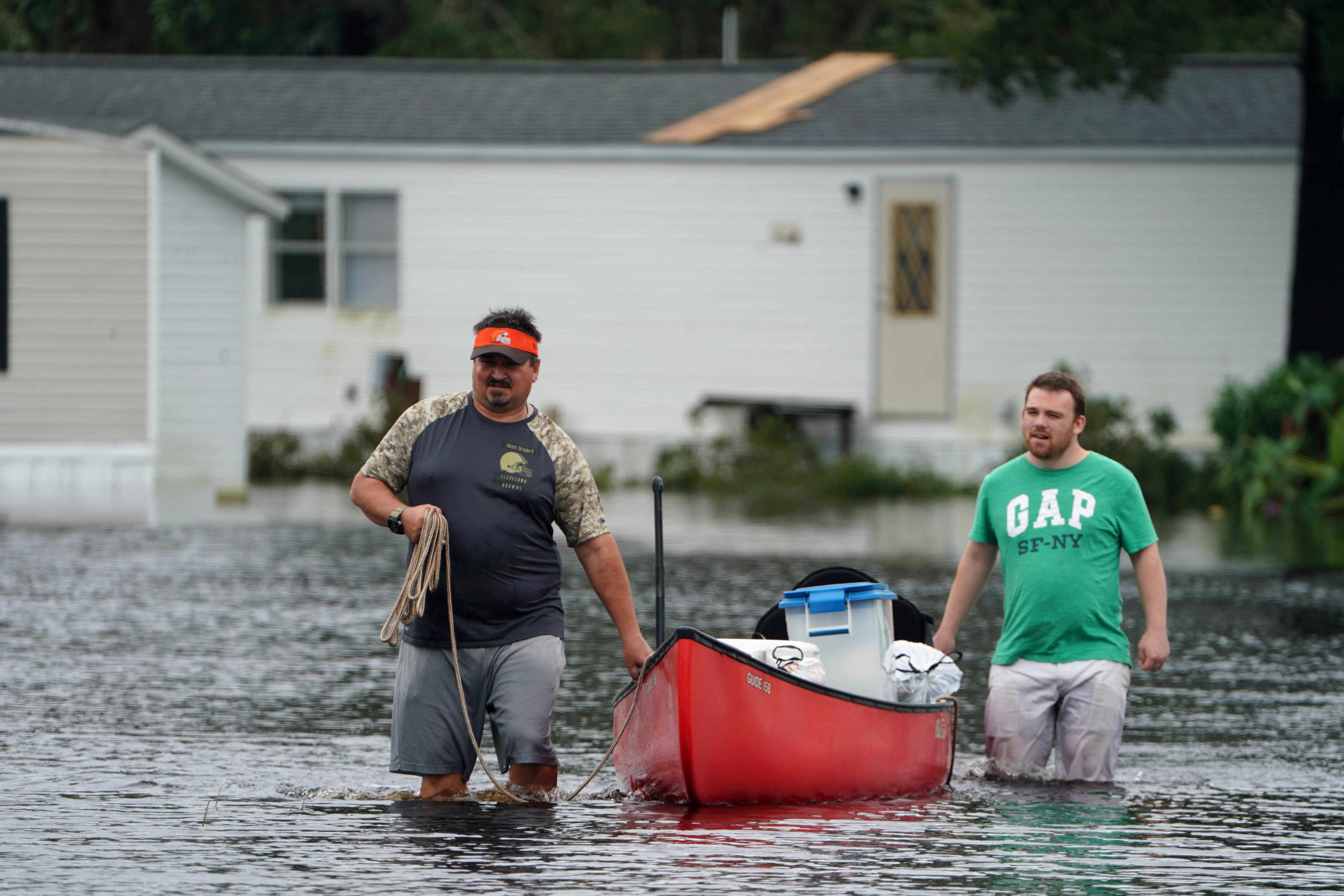 People walk through flooded street after Hurricane Florence struck Piney Green