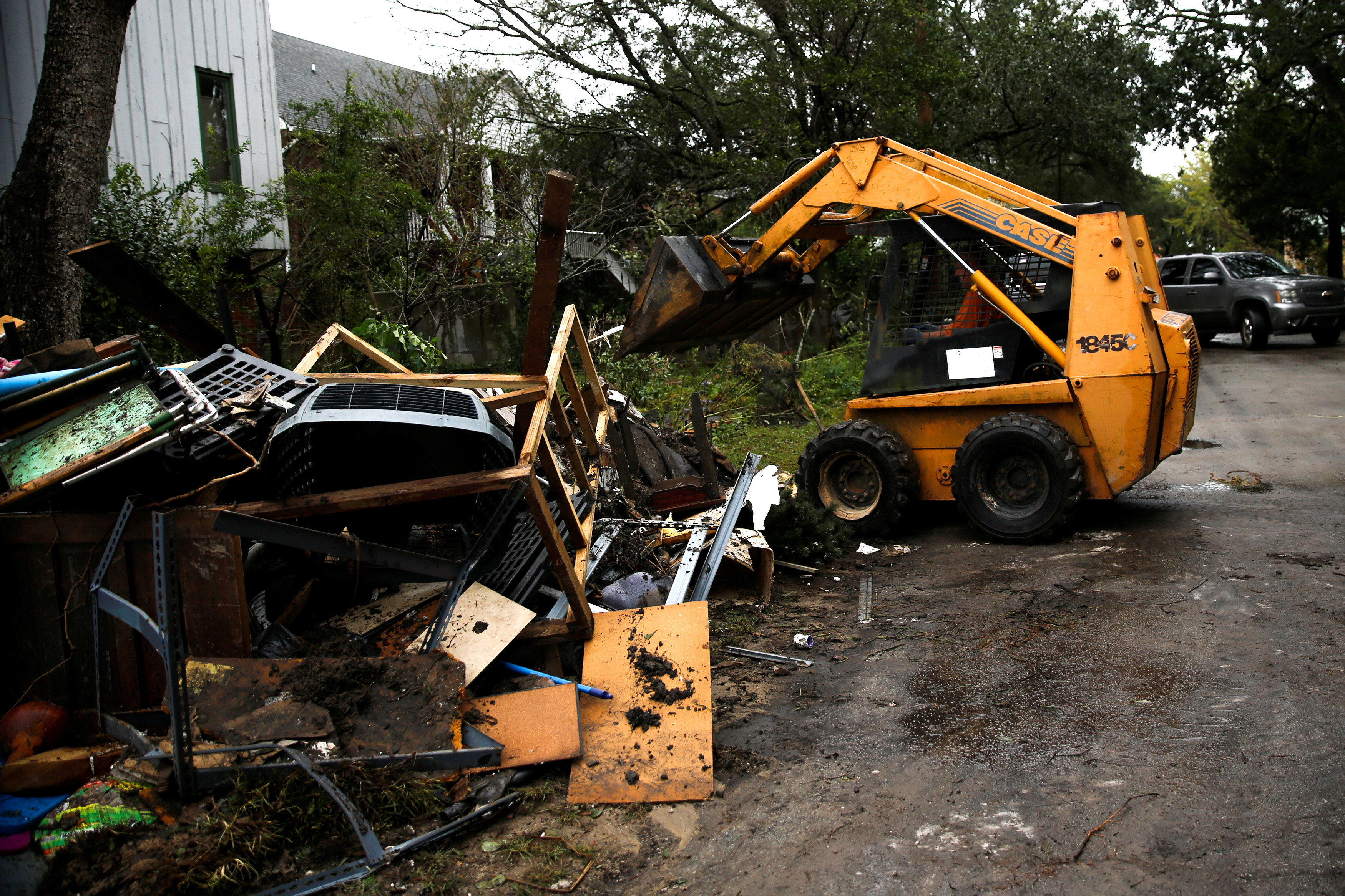 People use a backhoe to clean their house after Hurricane Florence in New Bern