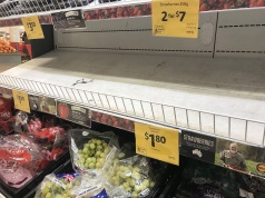Empty shelves, normally stocked with strawberry punnets, are seen at a Coles Supermarket in Brisbane