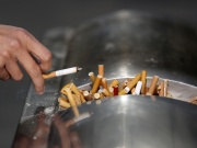 A man flicks ashes from his cigarette over a dustbin in Shanghai