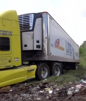 A truck leaves with an abandoned trailer full of bodies that has been parked in Tlajomulco de Zuniga, Jalisco