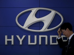 A car dealer stands in front of the logo of Hyundai Motor at its dealership in Seoul